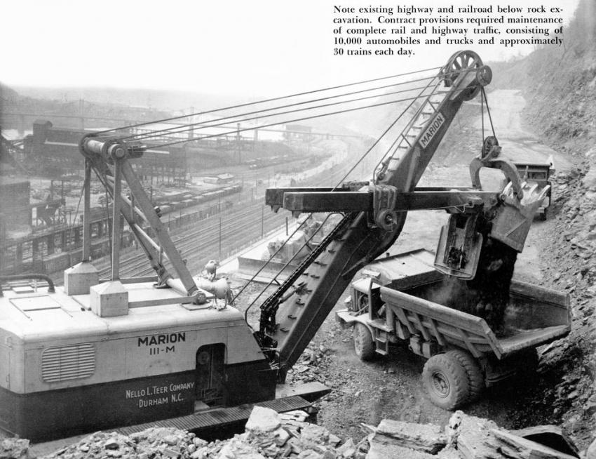 A Marion 111-M shovel loads broken rock into a Euclid 22-ton rear dump on the 2.5 mile Constitutional Boulevard project.