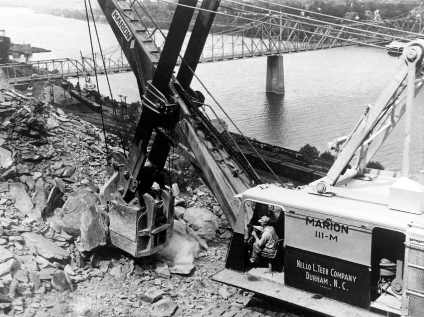 One of the two Marion 111-M four cu. yd. shovels used on the highway project which required 3,300,00 cu. yds. of excavation, all of which was waste material. The shovel is perched on a cliff-like bench high above the Ohio River.