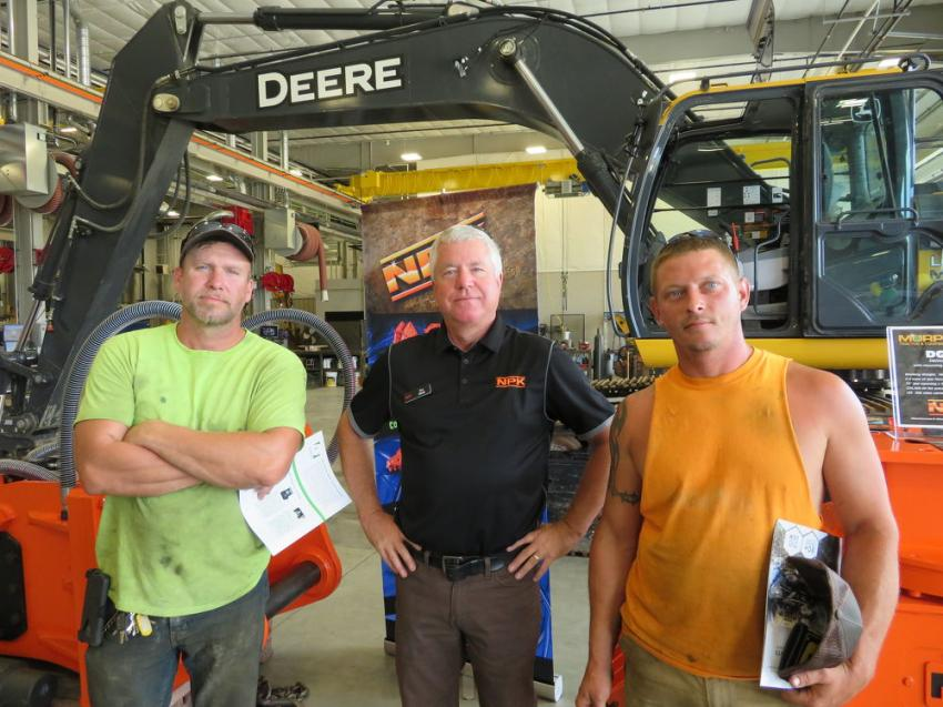 Ken Skala (C) of NPK Construction Equipment Inc., shows the NPK product lineup to Chris Bartosik and Ernest Whitt, both of RS Construction.