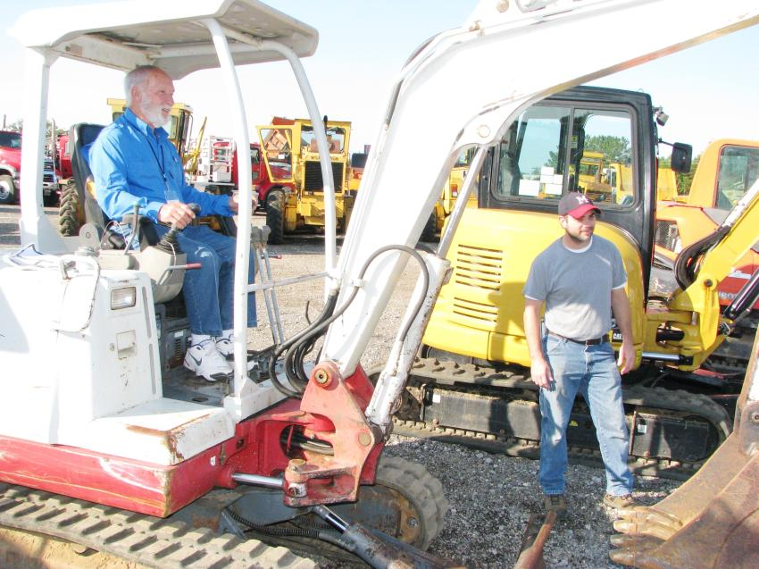 A couple of independent contractors out at auction looking for machines and test operating a Takeuchi TB125 of interest are Ed Hodge (in cab) of Laurel, Miss., and William Grice of Brookhaven, Miss.