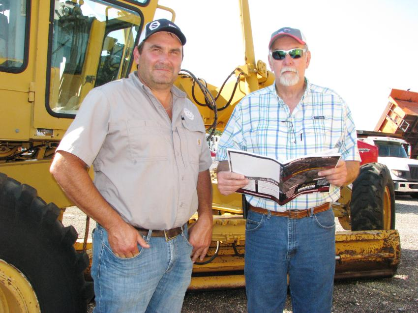 Looking over their auction catalogues and the machines on the auction yard are Dwayne Ellis (L) of Ellis Dozer Service, Seminary, Miss., and Pat Welborne of Welborne Inc., Petal, Miss.