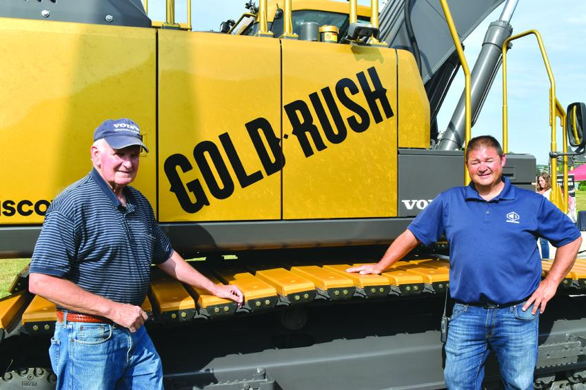 Stuart Welch (L), past president of Chadwick-BaRoss, admires the Gold Rush excavator with Jeremy Jordan, general manager of Chadwick-BaRoss' Westbrook, Maine, facility.