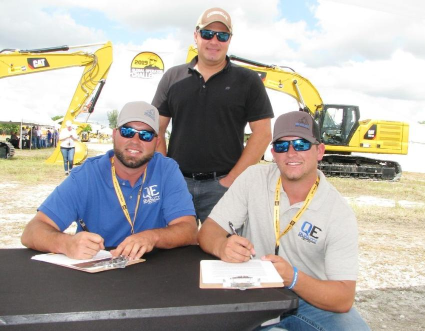 Signing in to compete in the challenge are Doug Richards (L) and Robert Emerson (R) of Quality Enterprises, Naples, Fla., with their Kelly Tractor sales representative Darryl Walters.