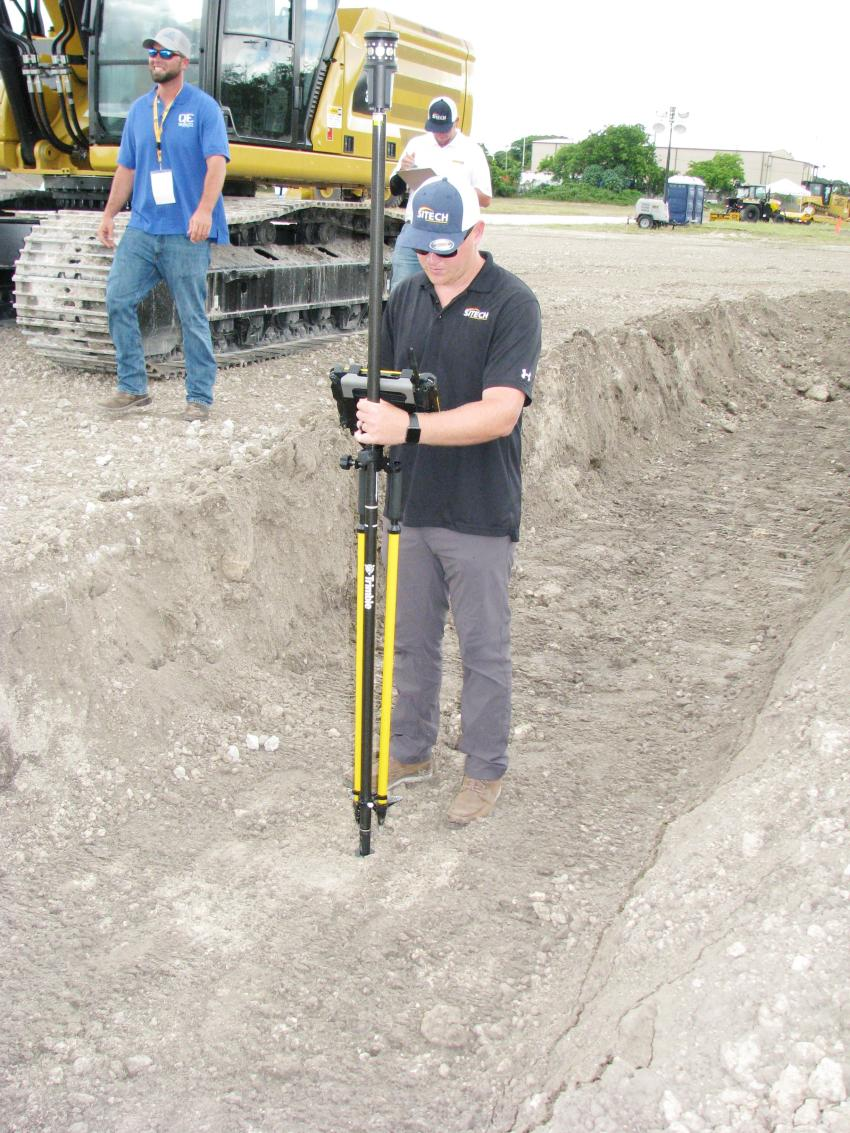 Stephen Miraglia of SITECH South checks the depth of the trench in the Cat 336 excavator challenge before the scoring can be tabulated and confirmed.
