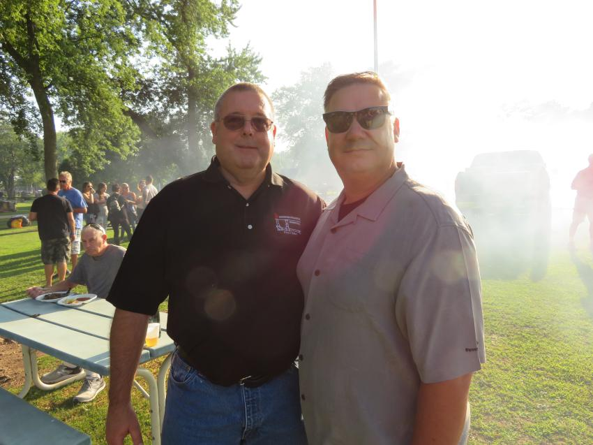 Dan Byrnes (L), sales manager of Underground Pipe & Valve, and Jason Cox, partner of Len Cox & Sons Excavating and Chairman of the Board of CAWGC catch up during the Annual Steak Fry event.