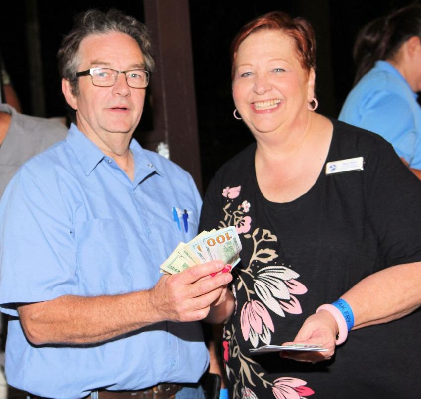Mary Metz (R), CAWGC executive director, presents the prize to 50/50 winner Gary Adams of Cecchin Plumbing.