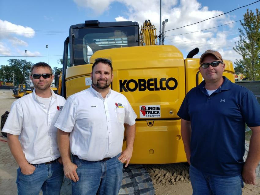 (L-R): Michael Hennessey of Illinois Truck & Equipment Co.; Mark Mitchell, sales manager of Illinois Truck & Equipment Co.; and Dan Breunig of the Sandwich Fair Association Board look over this Kobelco SK85-7 excavator.