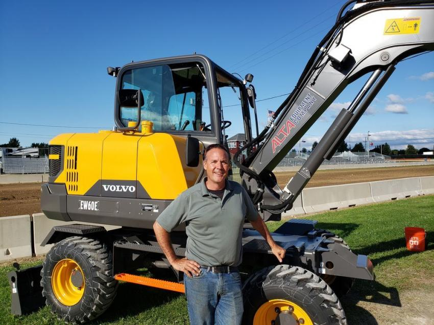 James May of Alta Equipment Co. stands next to the Volvo EW60E wheeled mini-excavator.