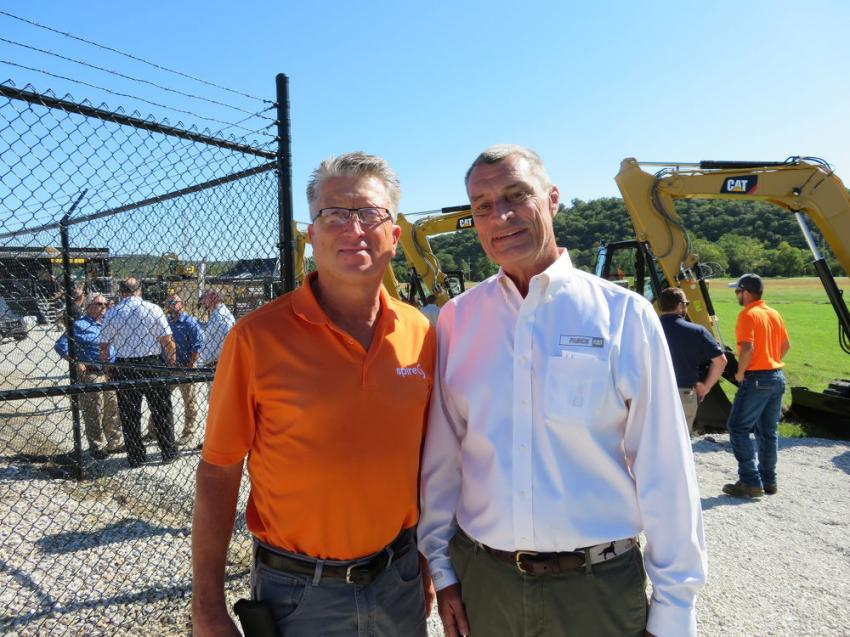 John Fabick IV (R), senior vice president of Fabick Cat, welcomes Randy Cox of Spire Energy to the Caterpillar 'In the Trenches Tour' featuring the next generation of mini-excavators in Fenton, Mo.