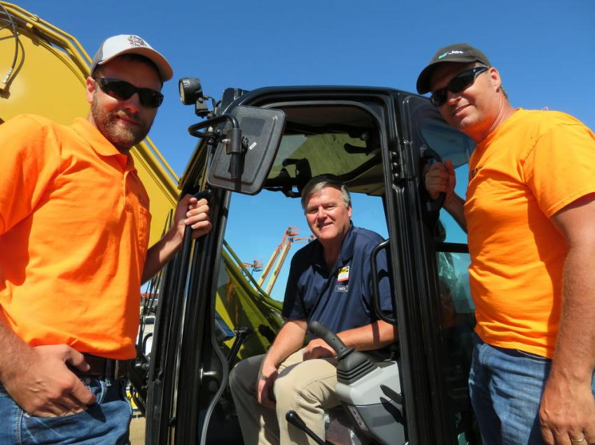 Jim Masters (C) of Fabick Cat goes over all the new features of this Cat 310 mini-excavator with Luke Struckhoff (L) of Lamke Trenching & Excavating Inc. and James Boyer of Integrity Septic & Sewer.