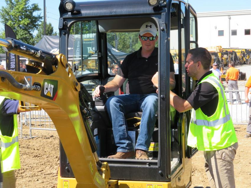 In the cab of this Cat 302 mini-excavator is Scott Ravenscraft (L) of Raven Contracting and answering all of his questions is Mark Perkes of Caterpillar.
