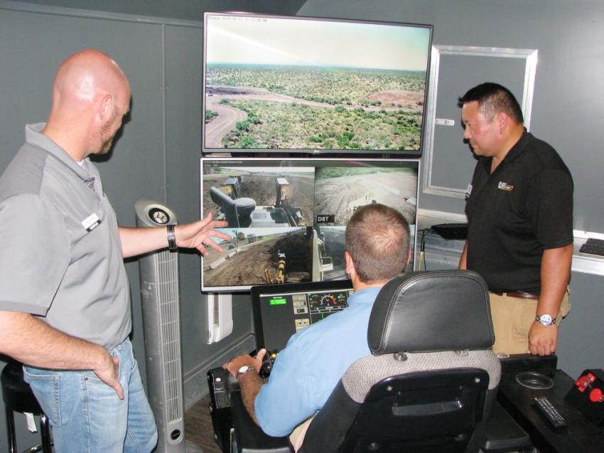Jeff Pirro (L) and Alan Pumklin (R) of Caterpillar provide Justin Evers of W.S. Newell & Sons, Montgomery, Ala., some coaching on remote operation of a Cat D8T dozer in Arizona from the Cat Take Command — Remote Control Operation trailer that was set up at the challenge event.