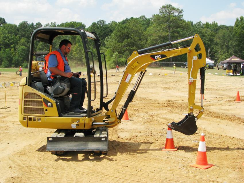 Jamie Carter of Carter Construction, Lynn Haven, Fla., finesses the bucket of a Cat 301.7D mini-excavator for picking up a golf ball in the Control To A Tee challenge.