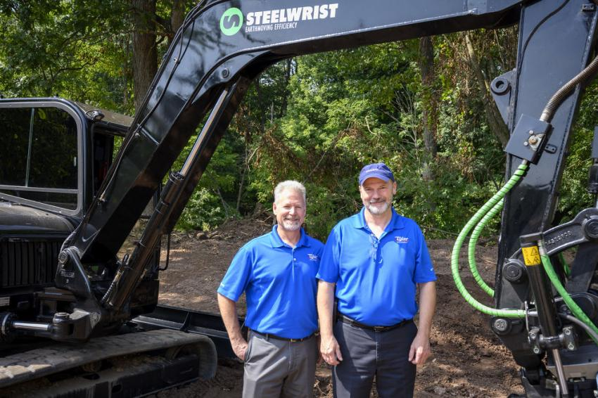 Larry Drapeau (L), CFO and account coordinator of road construction equipment, and Roland Mason, account coordinator of excavators, both of Tyler Equipment, stand in front of a Volvo ECR88 excavator.