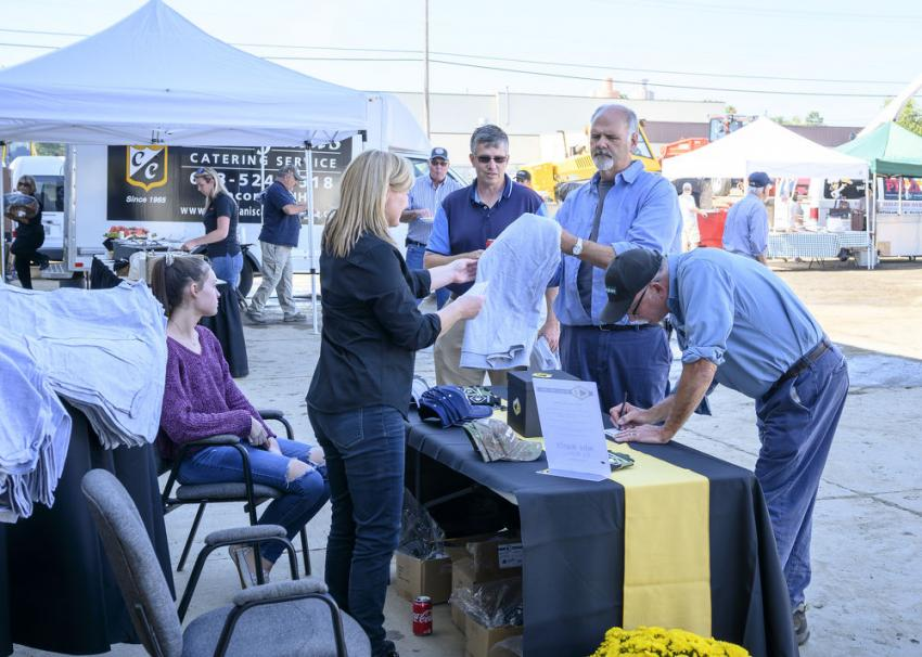 Attendees sign up for giveaways such as a golf bag, a fire pit, a corn hole set and more.