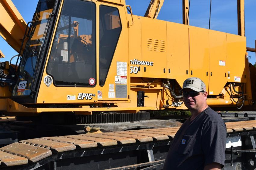 Jim Osborn, equipment manager of Kiewit, Sterling, Va., looks at two cranes that he believes Kiewit once owned. Typically, these cranes are red, but Kiewit is known for custom painting its cranes yellow.