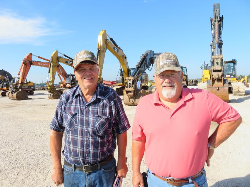 Walking the auction yard and looking over the wide range of iron and trucks are Lorin Warnkes (L) of Warnkes Farms and Chuck DeBolt.