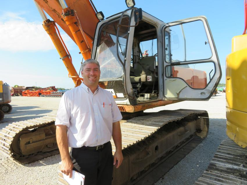 Jeremy Burkholder has a look at the excavators at the Sept. 18 auction in Morris, Ill.