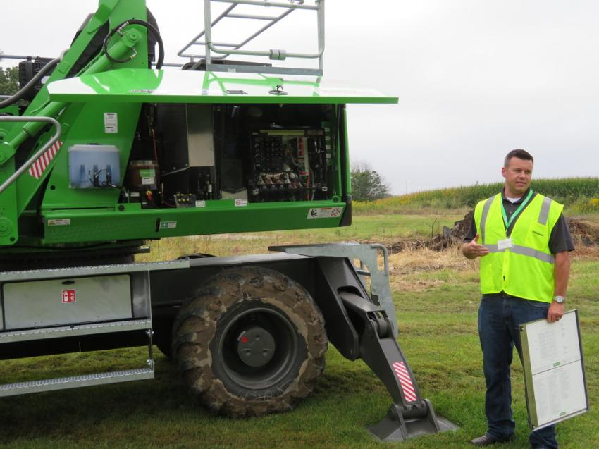 Darren Sudduth, manager of the tree care industry of Sennebogen, points out the engine features of the Sennebogen 718E.