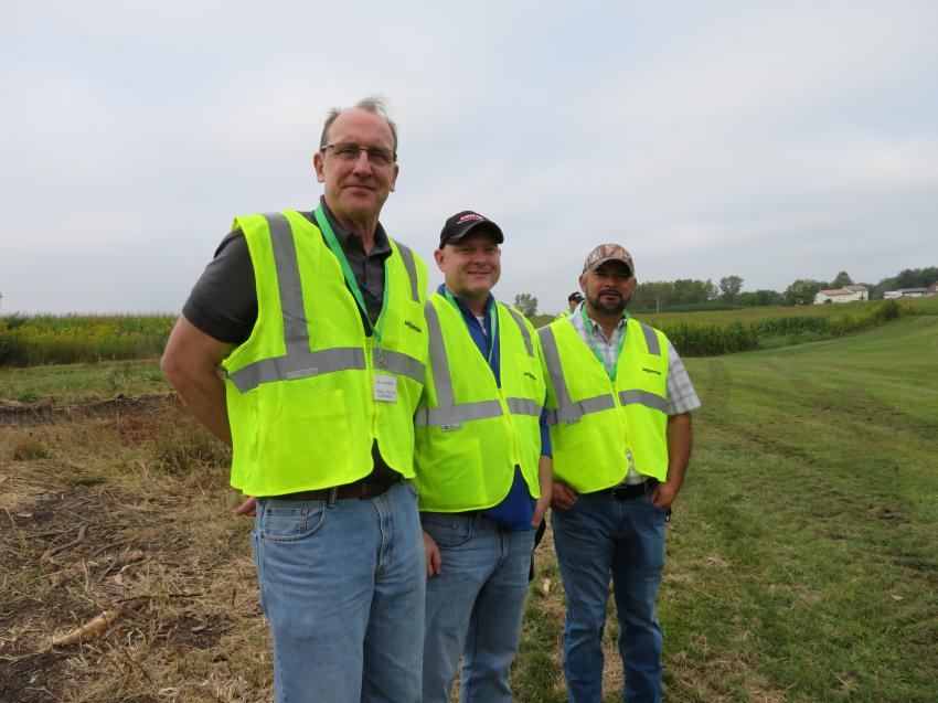 (L-R): Bill McNamara of Howell Tractor & Equipment and Rich Evans and Hugo Mora, both of Lewis Tree Service, wait for the demonstration of the Sennebogen 718E.