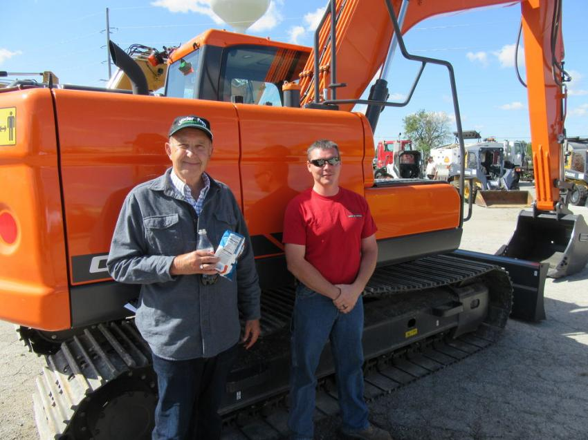 Roger Loecy (L) of Park Leasing Group joined Josh Peacock of Erie Black Top to review the low-hour equipment, including this Doosan DX140LC excavator at the auction.