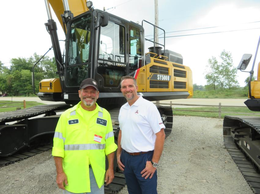 Josh Peddycord (R) of Sany America Inc., shows the Sany excavator line up to Chuck Pielet of Gaby Iron & Metal.