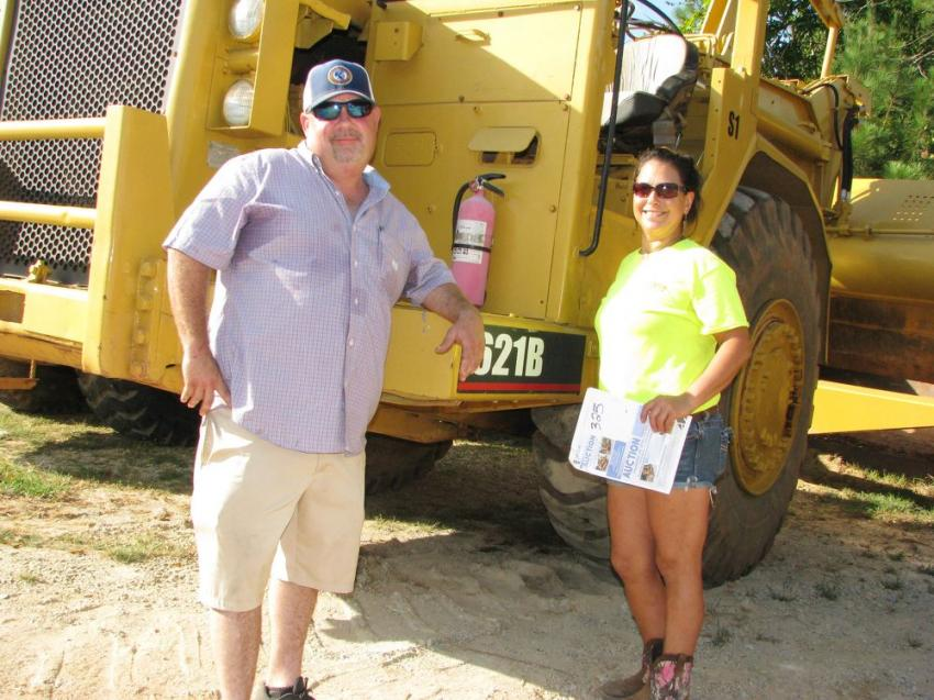 High bidder and the new owners of this Cat 621B scraper from Contour Grading and Pipe, based in Loganville, Ga., are Brian Yancey (L) and Betty Maldonado.