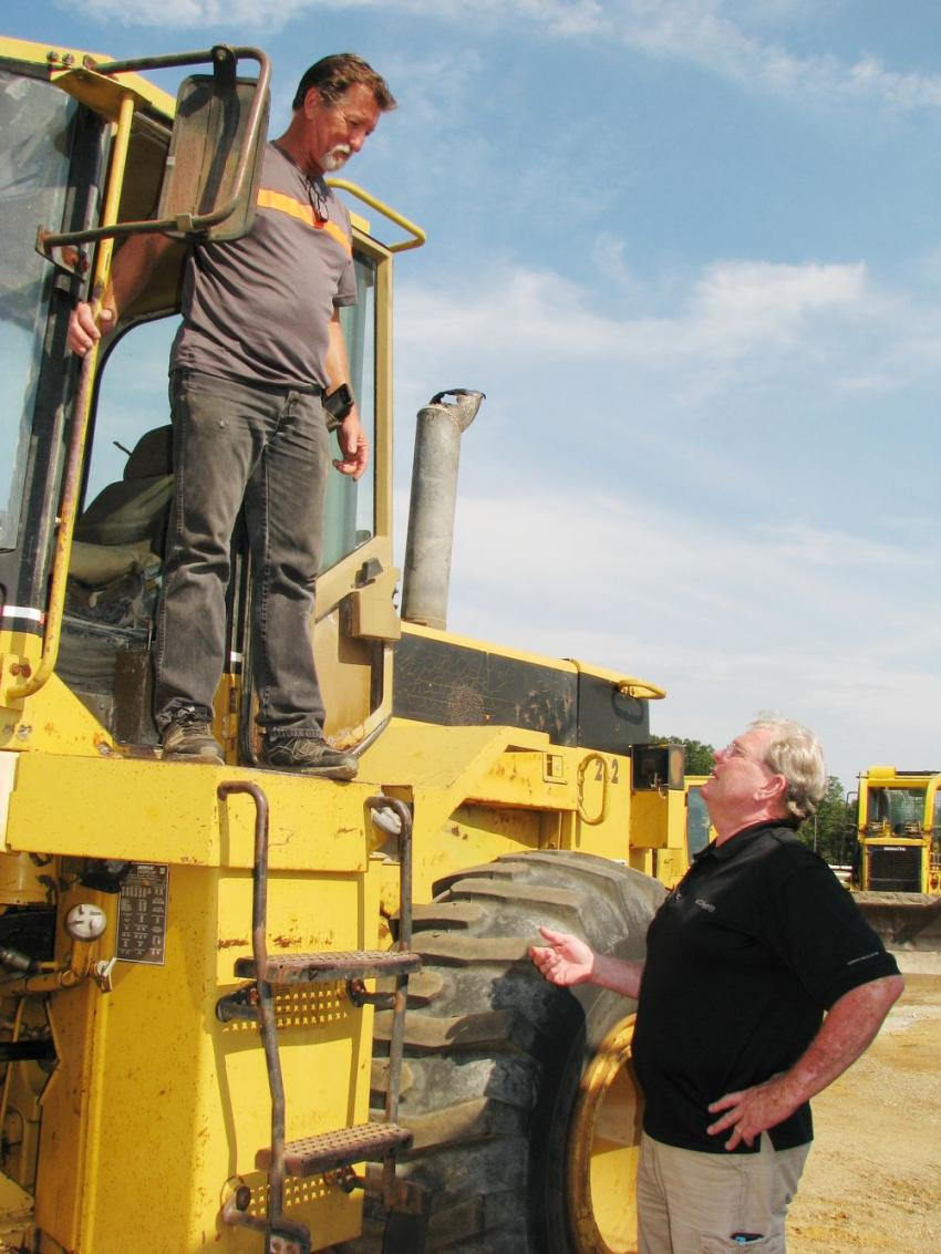 Jessie Cuevas (L), independent contractor based out of Long Beach, Miss., talks with Deanco Auction's Eddie Garner about a Cat 950F rubber-tired loader.