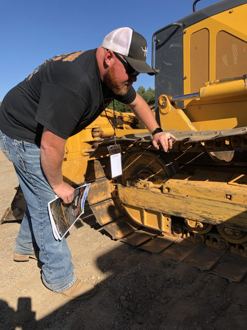 Dustin Brown of Brown's Excavating in Asheville, N.C., looks over the undercarriage on this John Deere 700J dozer.
