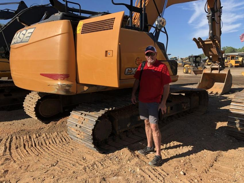 Chris Hawkins of Carbon Tek USA in Greer, S.C., checks out the engine on this Case excavator.  He liked what he saw and planned to bid on it.