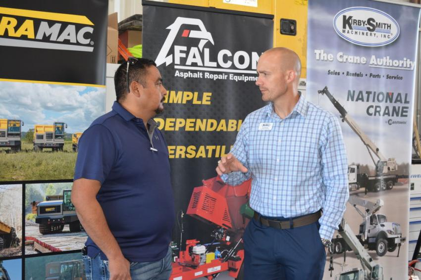 Bryce Puckett (R), Kirby-Smith's general manager, rentals, chats with Carlos Vegas, product service manager, crushing and screening, Kirby-Smith.