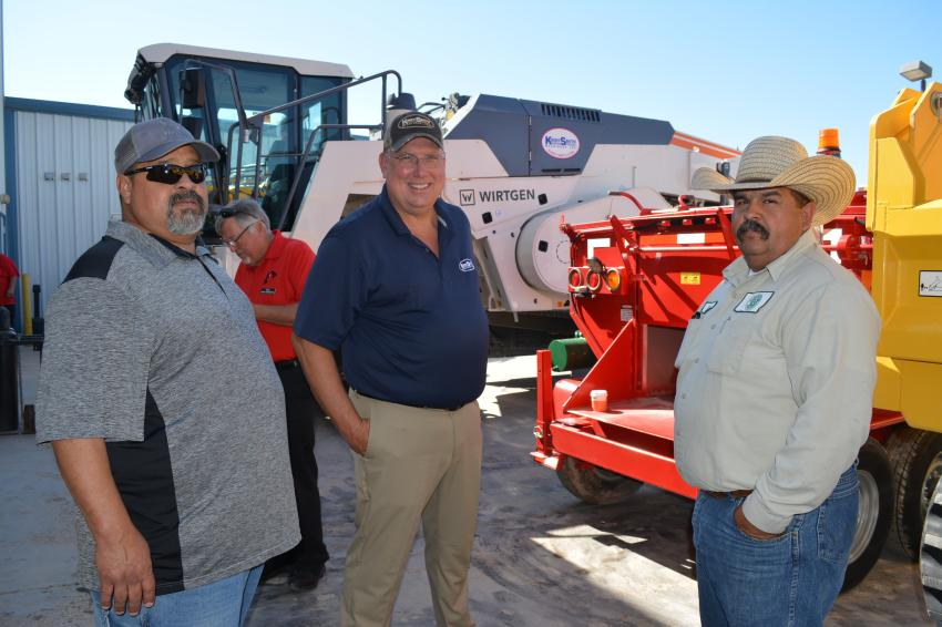 Dan Thompson (C) talks paving equipment with representatives of Ward County, Texas., highway department. Thompson handles governmental sales for West Texas.