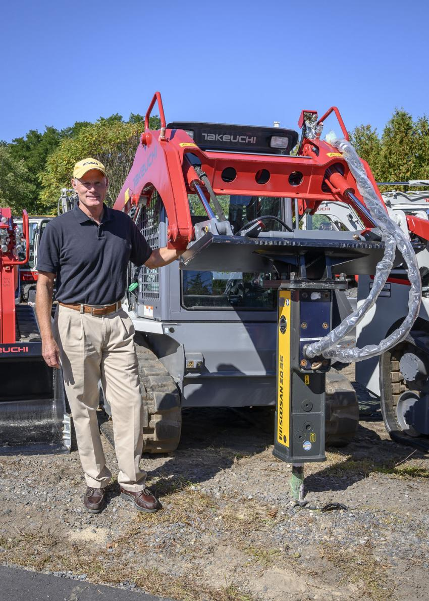 Greg Henry, director of sales and marketing of Soosan, stands with a Takeuchi TL8 compact track loader with a Soosan SQ35 hammer attachment.