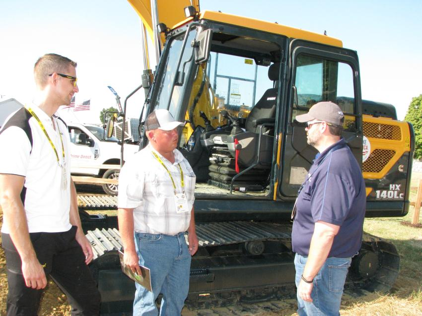 The new Hyundai HX140 LC was introduced at ICUEE and this particular unit was equipped with an Engcon quick coupler tiltrotator attachment. (L-R) are Engcon North America's Per-Oskar; Steve Alig, Pioneer Telephone, Kingfisher, Okla.; and Chad Parker, Hyundai Construction Equipment Americas, Norcross, Ga.