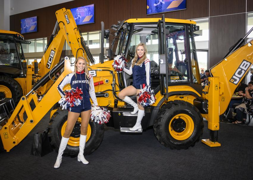 New England Patriot's cheerleaders Ashley B. and Morgan D. on the JCB 3CX.