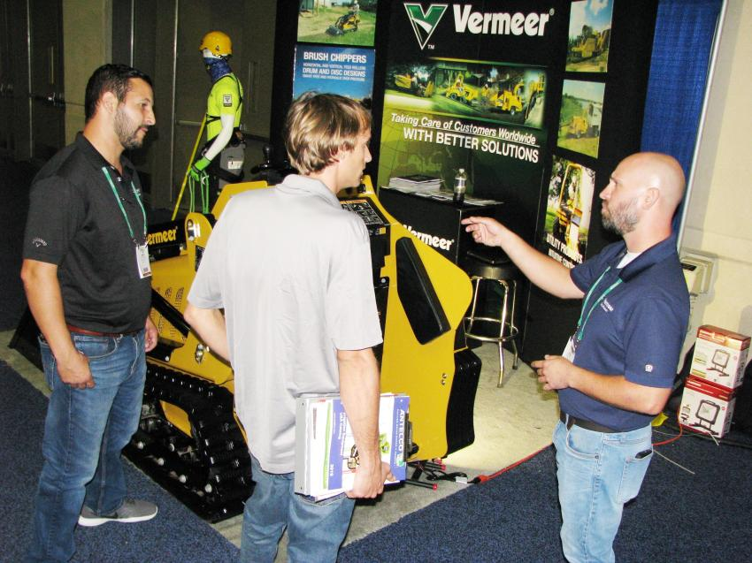 Michael Varela (L) and Josh Petit (R) of Vermeer Southeast provide a walk around demo of a Vermeer S925TX mini-skid steer to an interested show attendee.