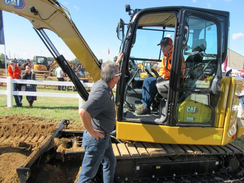Caterpillar's Greg Worley (L) discusses features of the new 306 mini-excavator with Glen Zumstein of Zumstein Landscaping at the show.