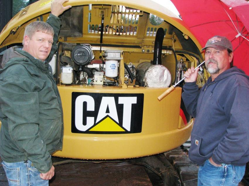 Going under the hood of a late model very clean Cat 308D CR mini-excavator are Jason Kelley (L) of Charles Kelley Construction, Blairsville, Ga., and Larry Allen of Allen Tanks & Supplies, Blue Ridge, Ga.