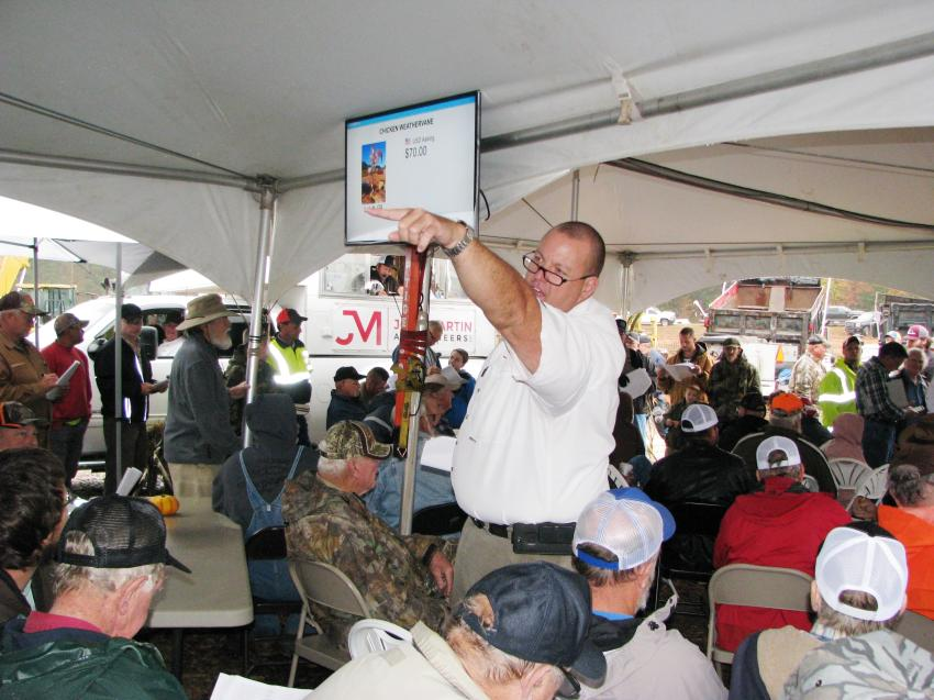 "Jason Stribling of Joey Martin Auctioneers finds another bid from the back row under the ""big tent"" as the harsh rains kept the auctioning under cover."