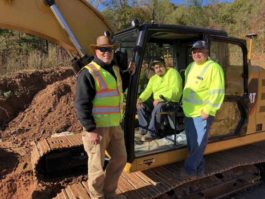 Steve Mitchell (L) of Carolina Cat is going over what's new on the Cat excavator with Ryne Sampson and Charlie Cook.