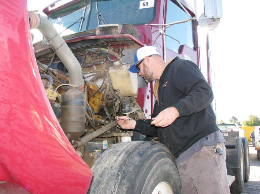 Regular attendee and customer of the Iron Auction Group, Rodney Mann of AEI Equipment, Rich Creek, Va., inspects a Kenworth W900 day cab truck-tractor of interest.