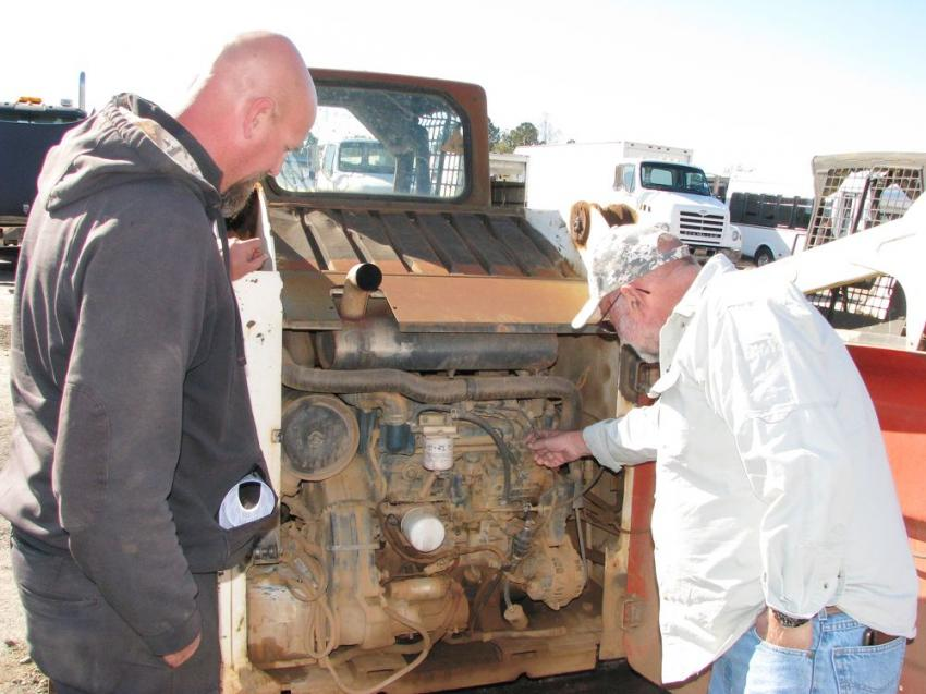 Recycling contractors Rick Woolard (L) and Ronnie Ray of Riverside Stump Dump, Asheville, N.C., look over a Bobcat T250 compact track machine.