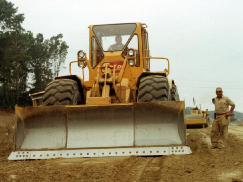 A Cardi Corporation 824B wheel dozer levels base material on the Route 140 project. A Rex vibratory compactor is in the background.