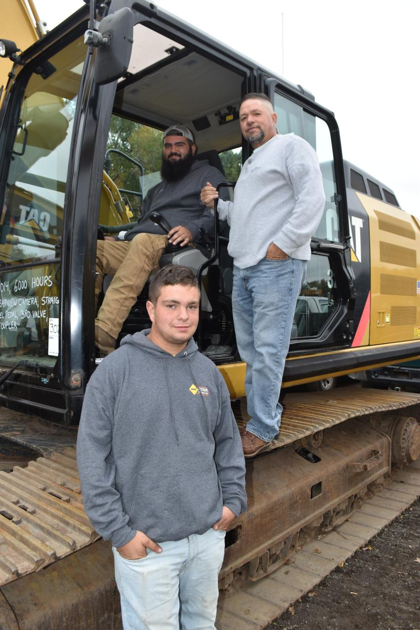 Checking out a Caterpillar 329E with S & F Construction in Weymouth, Mass., are Elson Fernandes, Louie Monteiro and Zack Silva.