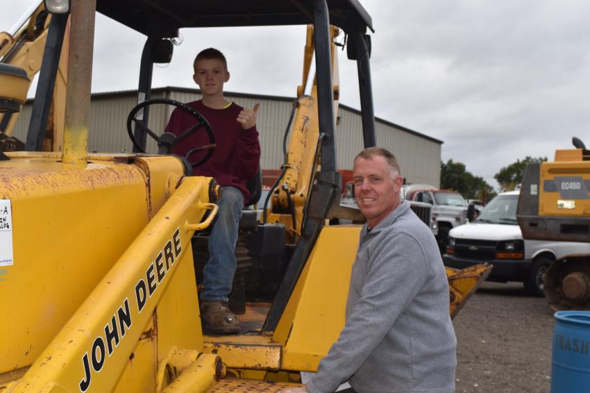 Junior operator Rylan Bell (L) gets the feel of a classic John Deere tractor loader backhoe while at the auction with his cousin Don Truskauskas, of Autumn Contracting in Arlington, Conn.