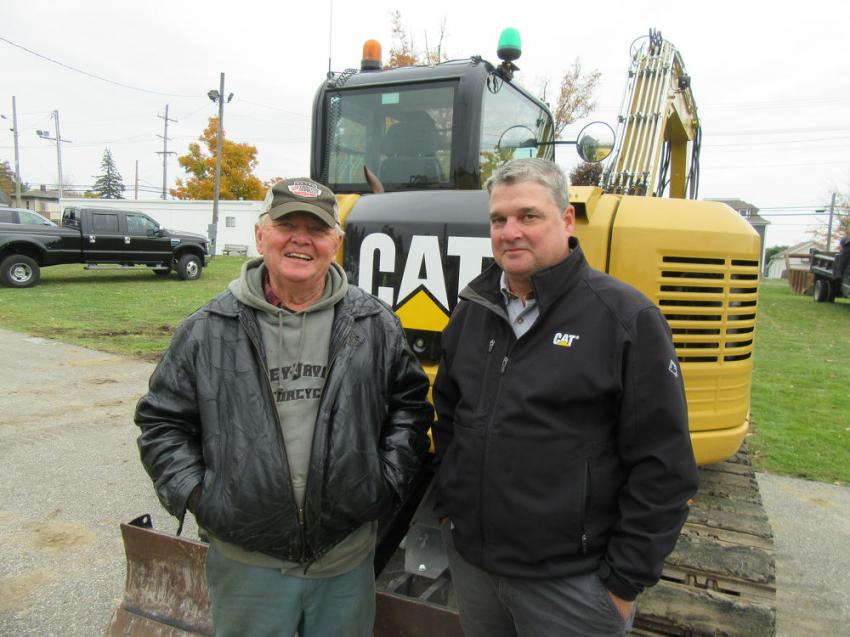 Jim Podojil (L) of Podojil Excavating and John Filby of SITECH Ohio look over this Caterpillar 308E2 CR excavator at the auction.