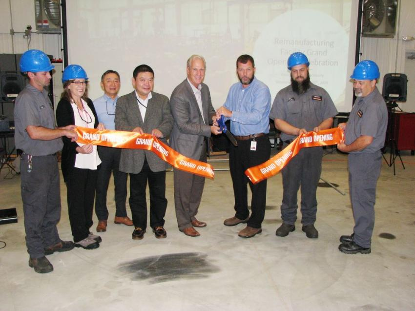 Al Quinn and Gregg French share the big scissors and cut the ribbon for the opening of the new remanufacturing facility.
