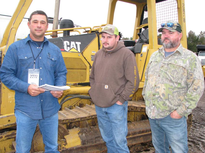 Looking over some of the dozers being auctioned (L-R) are Chris Hudson of Hudson & Hudson Contracting, Lucedale, Miss.; and Mack Anderson and Andy Anderson, both of Anderson Trucking, Wade, Miss.