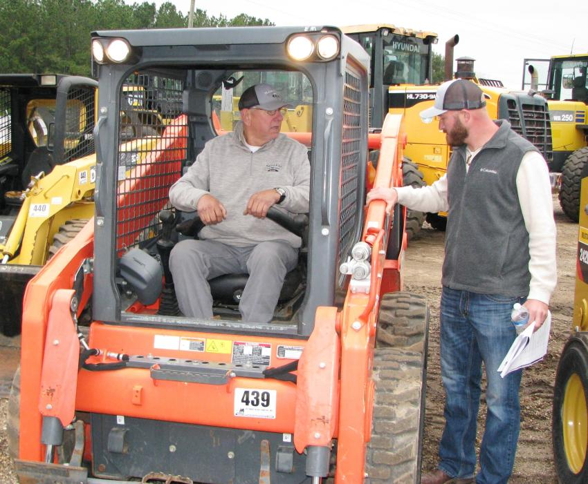 Checking out a low-hour Kubota SSV-65 skid steer loader are Skully McLeod (in cab) and Dustin Helton of McLeod & Son Construction, Lucedale, Miss.