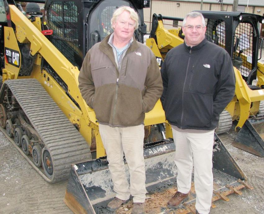 Inman Ellis (L) of Coastal Brush Cutting in Daphne, Ala., and his Thompson Tractor representative, Gulf Region Manager Tobie Sheils, stand in the bucket of Inman's newly purchased Cat 297D2 compact track loader.